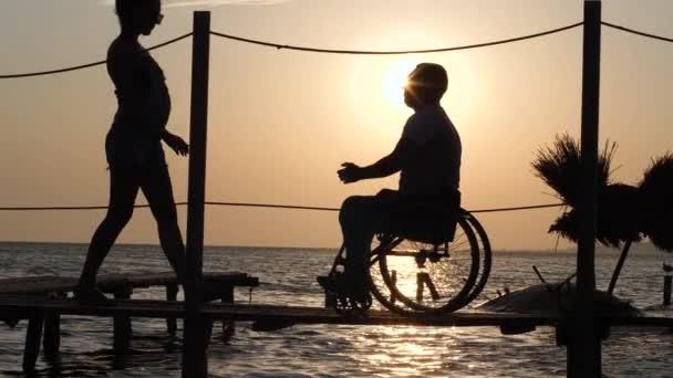 Romantisches Date von Frau mit Mann im Rollstuhl am Steg am Meer gegen den sommerlichen Sonnenuntergang