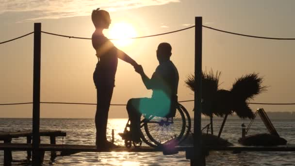silhouette of female and male handicapped on wheel chair holding arms and look at horizon in sea