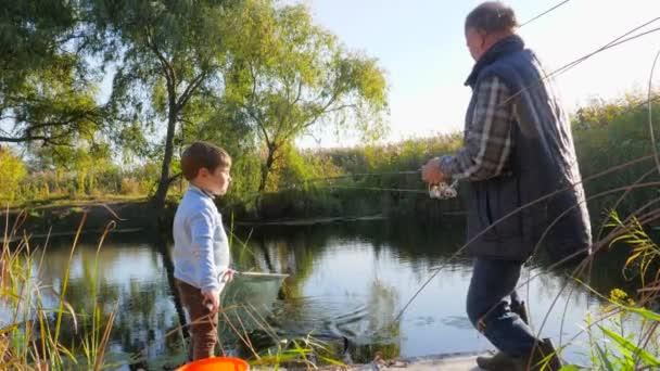 Sommerangeln am See, Opa mit Enkeln vergnügen sich bei warmem Wetter in der Natur