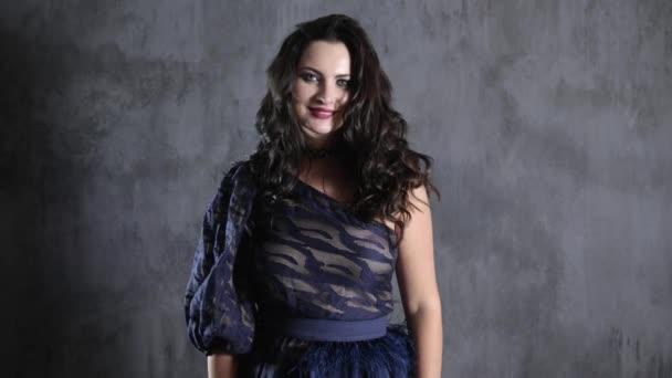 donna sorridente in abito chic e con trucco in piedi su sfondo grigio parete