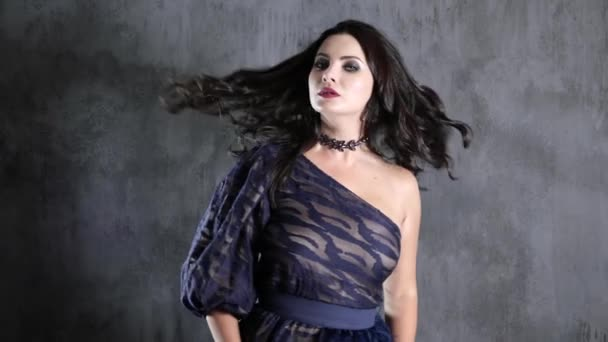 žena s krásným účesem a dekorace na krku se otáčí na pozadí šedé zdi