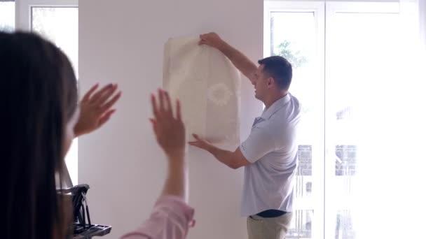 Wohnungsverbesserung, junger Mann probiert neue Tapeten an der Wand an, während Frauen bei Renovierungsarbeiten in Wohnung mit Fenstern entscheiden