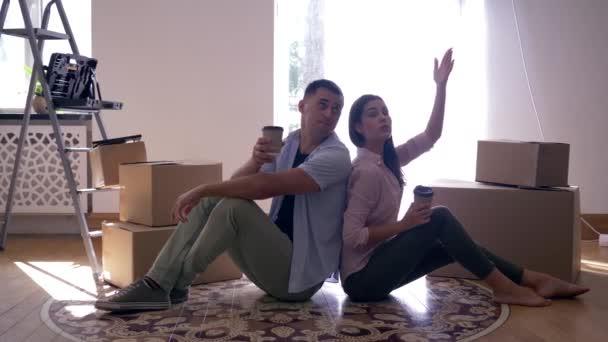 šťastná dívka s přítelem vychutnat nový domov a pití kávy sedí na podlaze mezi boxy po přemístění