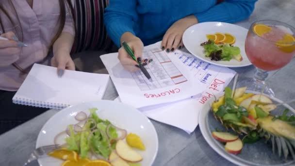 hubnutí samice s dietním plánováním kalendář počítat kalorie na listu papíru během zdravé jídlo