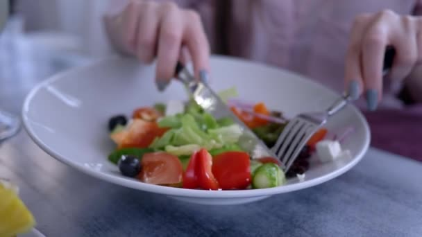 beautiful diet food, female hands with a knife and fork cut the fresh cucumber in Greek salad closeup