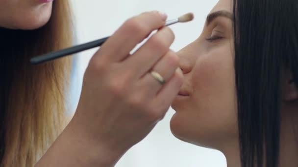 módní stylista Aplikovat kosmetiku make-up na oči modelu v beauty studiu