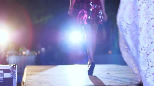 módní přehlídka, modelka s dlouhýma nohama v botách na vysokých podpatcích a lesklými šaty jde podél lávky