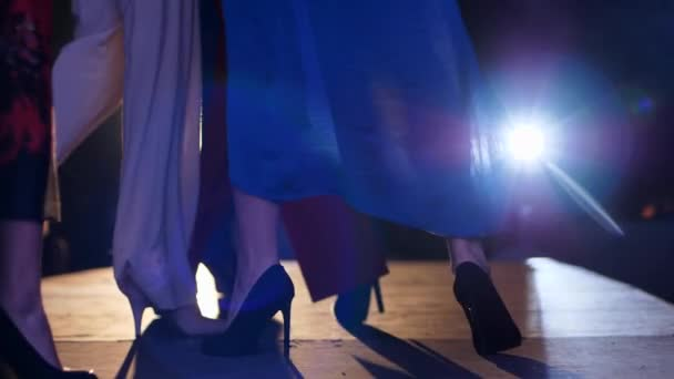 fashion show, feet of models in stylish high-heeled shoes on catwalk