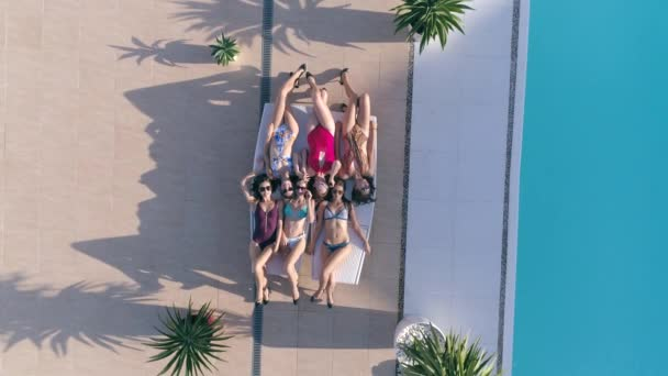 sunbathing, happy Friends girls into Swimsuit and sunglasses relaxing on lounger near Poolside at luxurious holiday