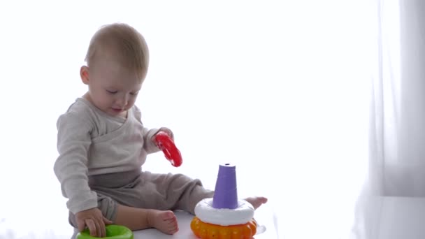 cute toddler played educational toys pyramid in bright room