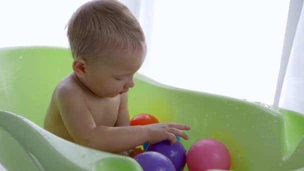 Kleiner Junge spielt mit farbigen Kugeln im Wasser, während er in Babybadewanne schwimmt