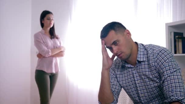 rodinné nedorozumění, zklamaný manžel po hádce s manželkou sedící doma skládající ruce blízko obličeje a žena stojící