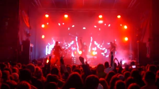 élő zene, sok ugráló emberek felfegyverkezve élvezze előadását rock művészek fényes színpadon