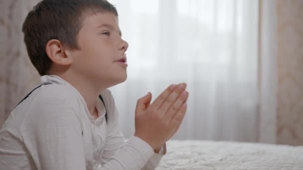 Gottvertrauen, betendes männliches Kind mit Hoffnung im Herzen und verschränkten Armen, betet zu Gott, der auf Rädern in der Nähe des Bettgestühls steht