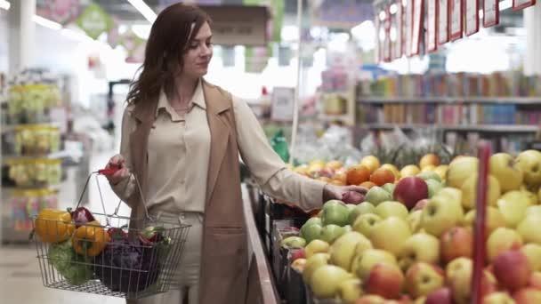 šťastná hospodyňka s nákupním košem nakupuje jídlo čerstvá zelenina a ovoce na regálech supermarketů