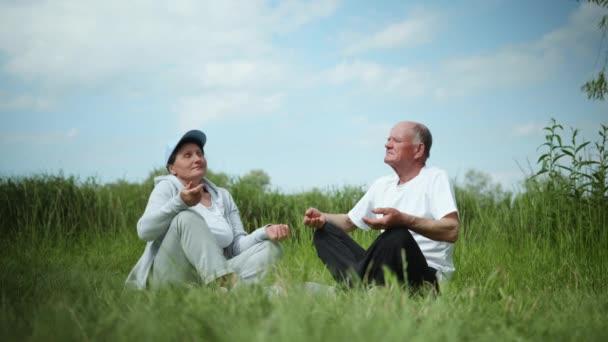 Gesunder Lebensstil im Alter: Ein älteres Ehepaar, das einen sportlichen Lebensstil liebt, macht im Freien auf einer Yogamatte auf dem grünen Rasen körperliche Übungen