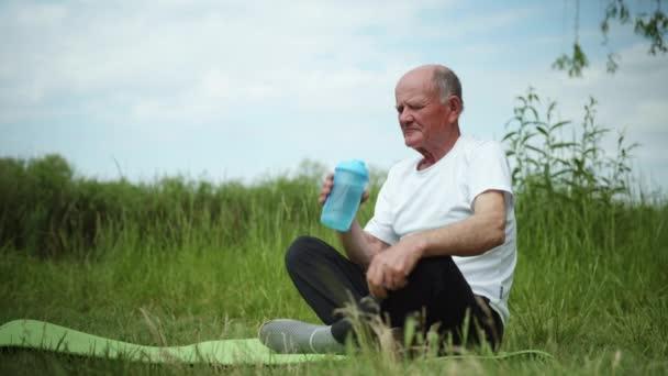 Lebensstil, gesunder älterer Mann trinkt nach Sport und Meditation auf der Yogamatte auf dem Rasen sauberes kühles Wasser aus der Flasche zur Sporternährung