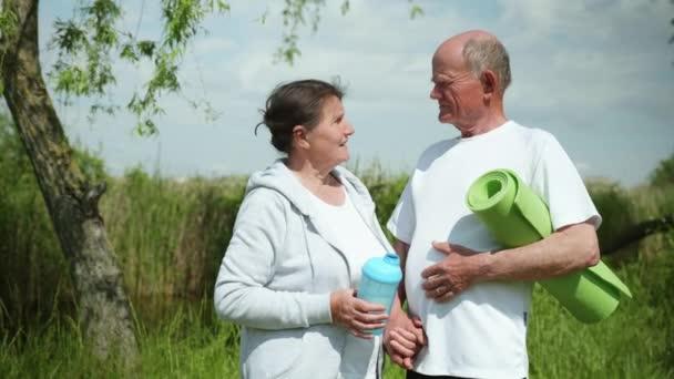 Gesundheitsversorgung, Porträt fröhlicher alter Menschen mit Yoga- oder Meditationsteppich in der Hand führen zu sportlichem Lebensstil
