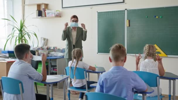 back to school, female teacher in glasses shows a pupils how to put on medical mask on face before lesson in classroom