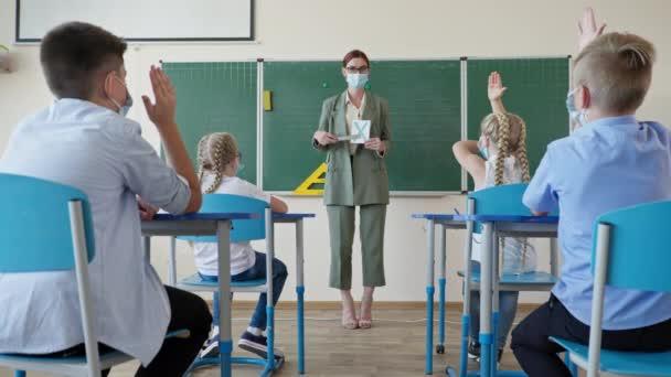álarcos tanár tanuló kártyákat mutat az osztály előtt álló betűkkel, a gyerekek figyelnek és felemelik a kezüket az óra alatt