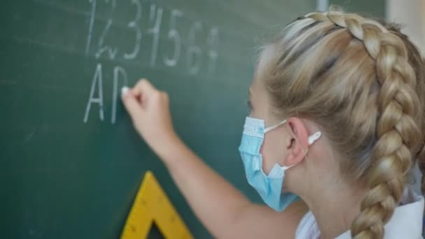 education after quarantine, schoolgirl in medical mask at the blackboard writes in chalk the English alphabet in classroom at school