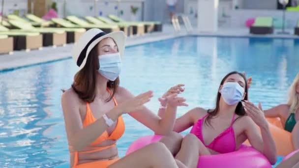 tengeri koronavírus, fiatal vidám barátnők visel védő orvosi maszkok vírus és fertőzés érezd jól magad a medencében úszás medencében