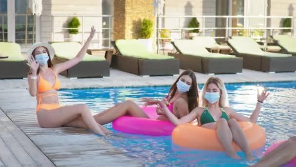 nyári koronavírus, gyönyörű fiatal nők viselnek orvosi maszkot, hogy megvédje a vírustól és a fertőzéstől élvezze luxus üdülőhely nyaralás úszni medencében