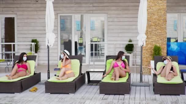 társadalmi távolság, gyönyörű fiatal női barátok fürdőruhában a napozóágyon