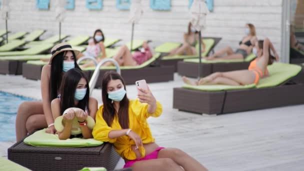 új normális, fiatal lányok tiszteletben tartják a biztonsági óvintézkedéseket, és visel orvosi maszkok és szelfi pihenés a napozóágyon medencével