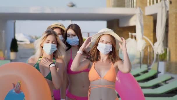 vakáció világjárvány idején, gyönyörű fiatal lányok fürdőruhában és orvosi maszkok, hogy megvédje a vírustól és a fertőzéstől pihentető nyári üdülőhely medencével felfújható gyűrűk emelése közben a