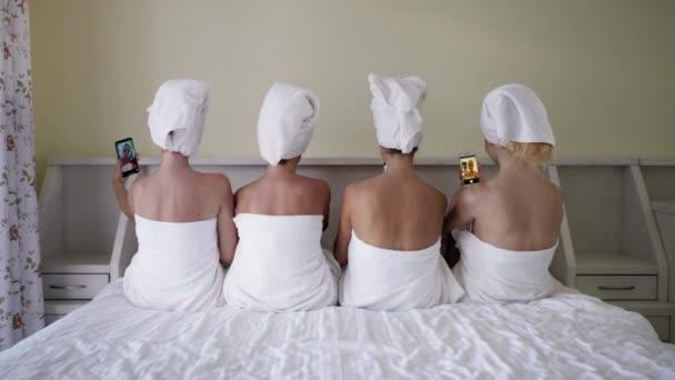 hölgy party, fiatal szép barátnők törülközőben a fejükön, hogy egy szelfi, miközben fekszik az ágyon okostelefonok