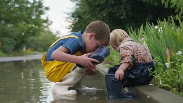 freundliche Kindheit, attraktiver Junge, der sich um seinen Bruder kümmert und Gummistiefel auszieht, die beim Spielen in der Pfütze Wasser ausschütten