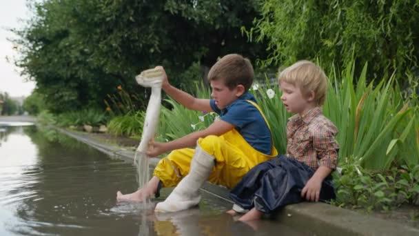 fröhliche freche Kinder spielen im Freien und gießen Wasser aus Gummistiefeln, während sie sich in der Pfütze vergnügen