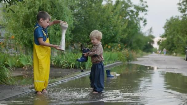 glückliche Kindheit, attraktive männliche Kinder in Latzhosen schütten Gummistiefel aus, nachdem sie nach Regen an einem warmen Tag bei schönem Wetter in einer Pfütze auf der Straße spielen