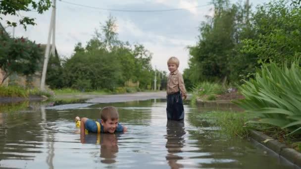 Kindheit, fröhlicher Junge bei guter Gesundheit, zusammen mit seinem kleinen Bruder, spielt gern und liegt an warmen Sommertagen nach dem Regen auf der Straße in einer Pfütze