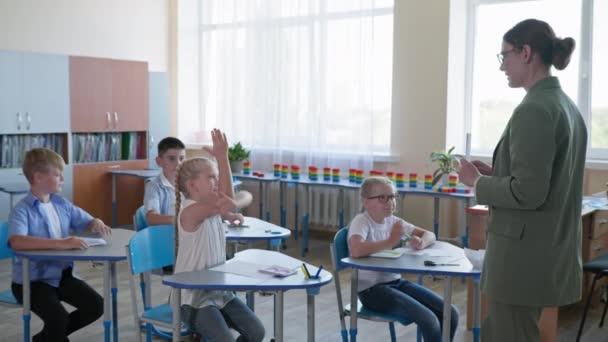 Grundschulklasse mit bunt gemischten, aufgeweckten Kindern, die dem Lehrer beim Unterricht zuhören, Schüler, die alle die Hand heben und die richtige Antwort wissen