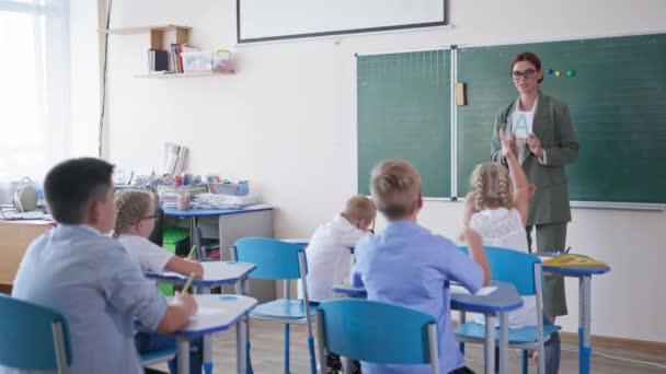 učitel ukazuje žákovské karty s písmeny u tabule ve třídě, děti zvednou ruku s vědomím správné odpovědi na lekci