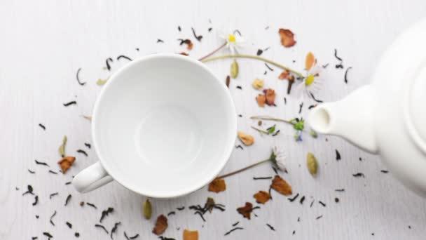 konvice čaj nalil do poháru na bílém stole