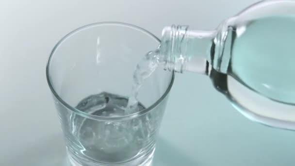 nalévání minerální vody do skla z láhve