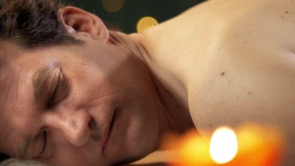 Mann empfangenden Rückenmassage im Wellnessbereich zu entspannen