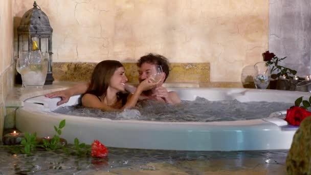 Šťastný pár opékání s bílou prosecco vnitřní bazén v hotelu