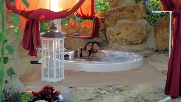 Couple in love enjoying vacation in exterior pool at sunset smiling looking camera slow motion