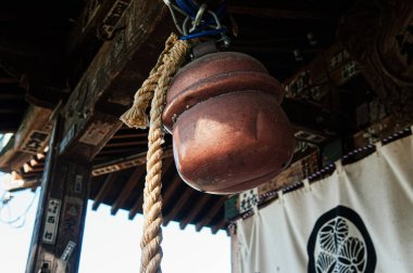 DEC 4, 2018 Aizu Wakamatsu, JAPAN - Old rusty antique Japanese bronze shinto bell or Suzu with rope hanging from wooden ceiling in Shrine at Tsuruga Jo castle