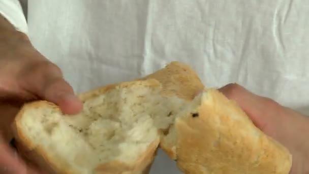Mens hands break a loaf of freshly cooked bread