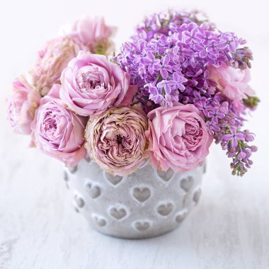 Close-up floral composition with a pink roses and lilacs