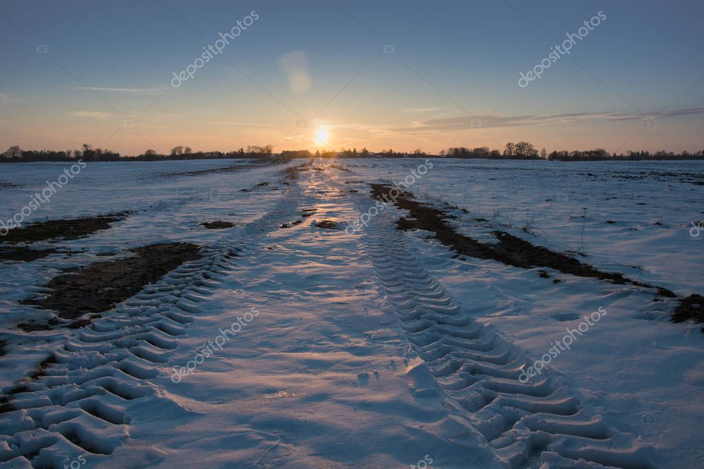 Wheel tracks on a snowy dirt road, horizon and sunset