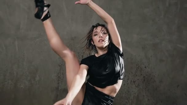 Tanečník mokré mladá dívka skáče na jevišti pod vodou kapky. Krásný mokrý tanečnice tančí emocionální tanec při pohledu do kamery