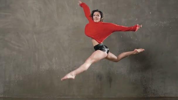 Eine nasse Tänzerin im roten Pullover macht einen Sprung im Regen und plätschert vor sich hin. das Tänzermädchen, das während des Tanzes auf der Bühne unter Wasser tanzte, blickt in die Kamera