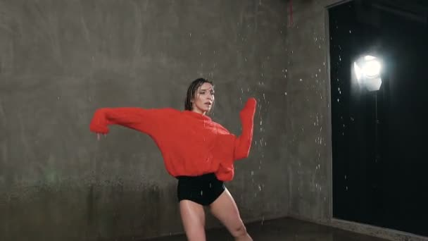 Professional female dancer who dances a modern emotional dance under the rain during training. Wet dancer girl in a red sweater dancing under drops rain in indoors