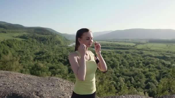 Corridore giovane donna in esecuzione in montagna lesercizio allaperto tecnologia indossabile fitness tracker. Atleta della donna in esecuzione al tramonto ascoltando musica con auricolari